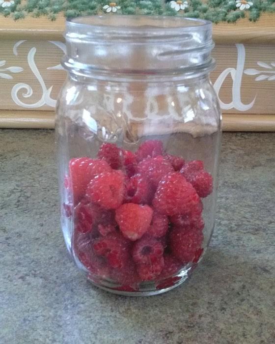 Raspberry honey jar half full